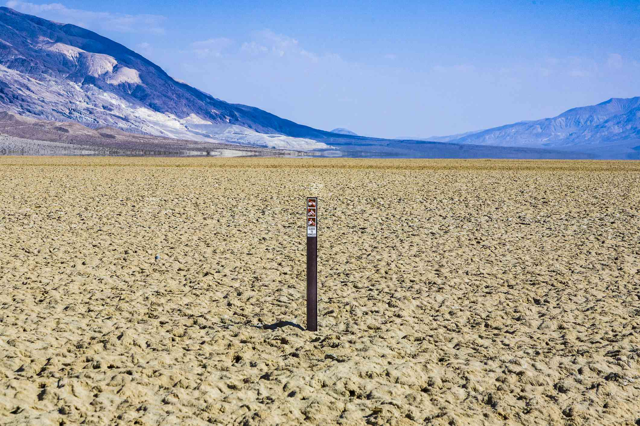 A dried up lake with a sign in the middle
