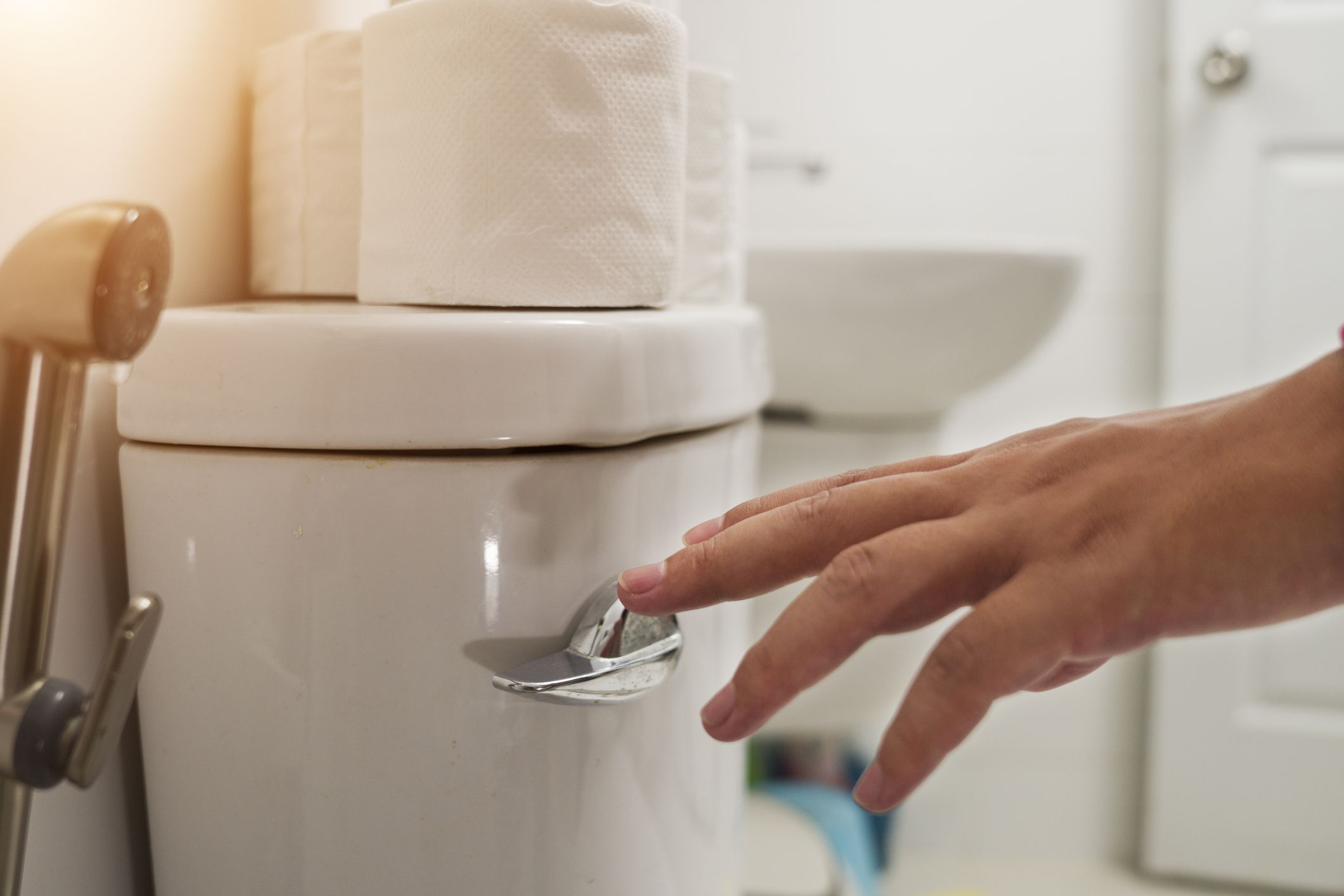 A white hand flushing a toilet with toilet paper sitting on top of it.