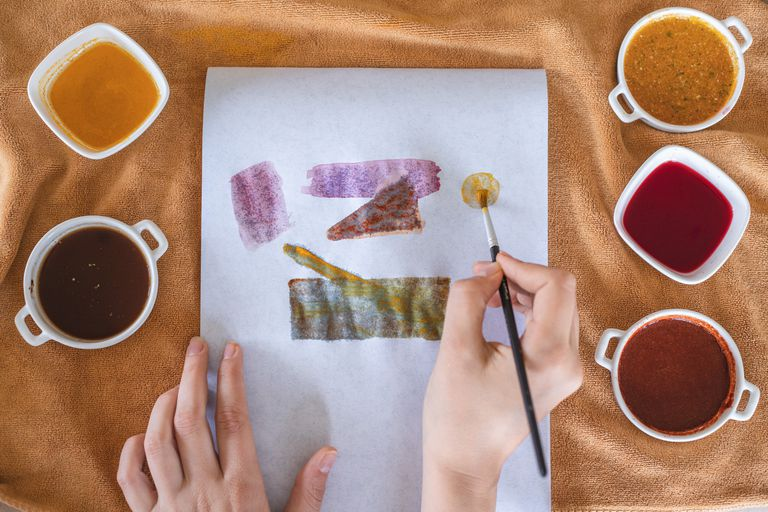 person uses various loose spices and water to create abstract spice painting on white paper