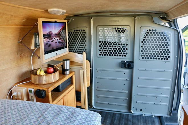 Work area in the van with a wall mounted computer and table with coffee and a bowl of fruit