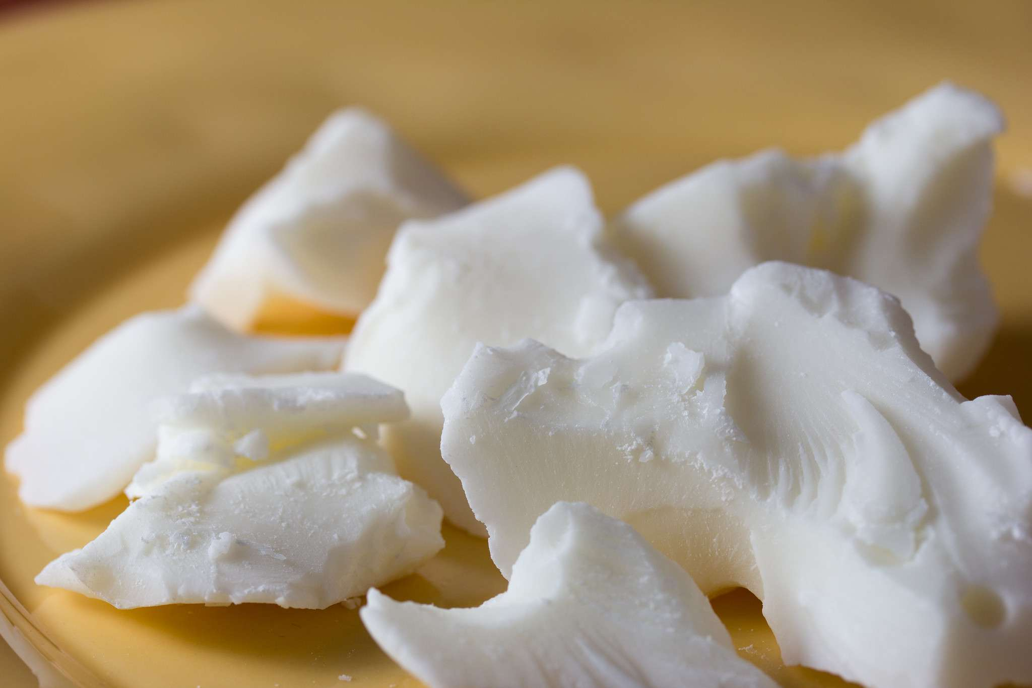 raw chunks of white cocoa butter up close on yellow plate