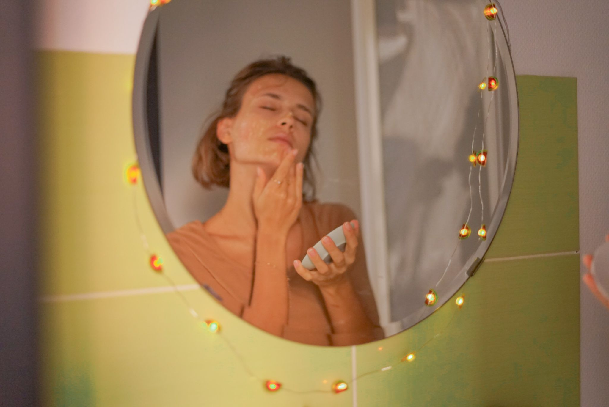 reflection in mirror of woman in bathroom rubbing honey on face for natural beauty treatment