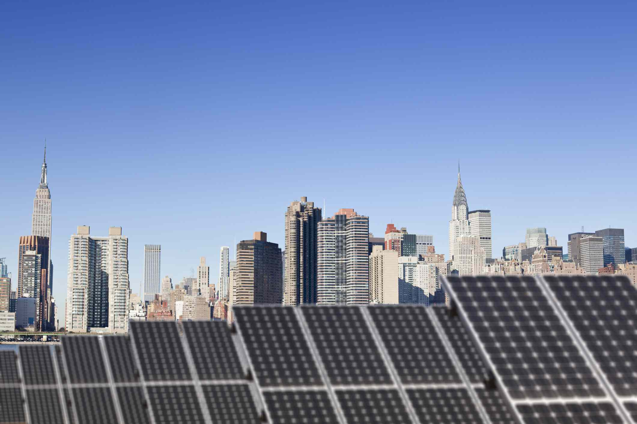 Solar panels on a roof with New York City in the background.