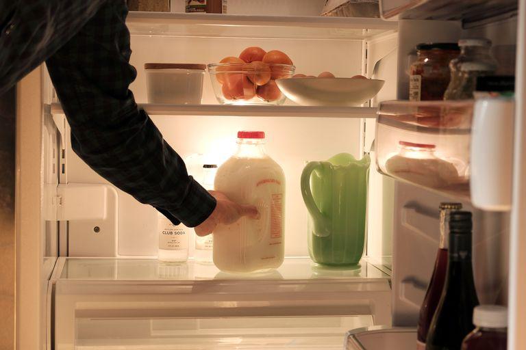 man puts glass milk in fridge