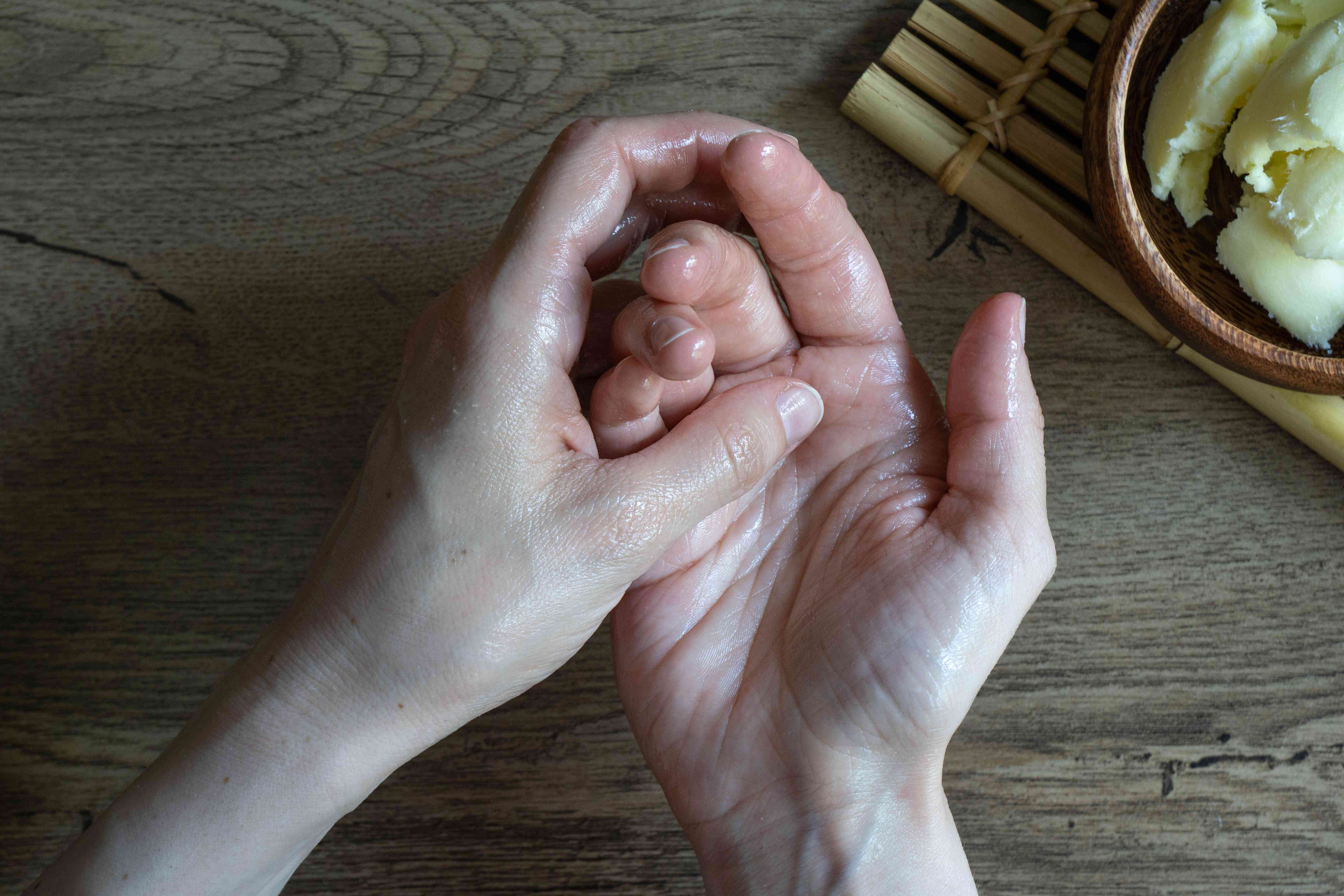 flat shot of dry hands rubbing in shea butter with wooden bowl nearby