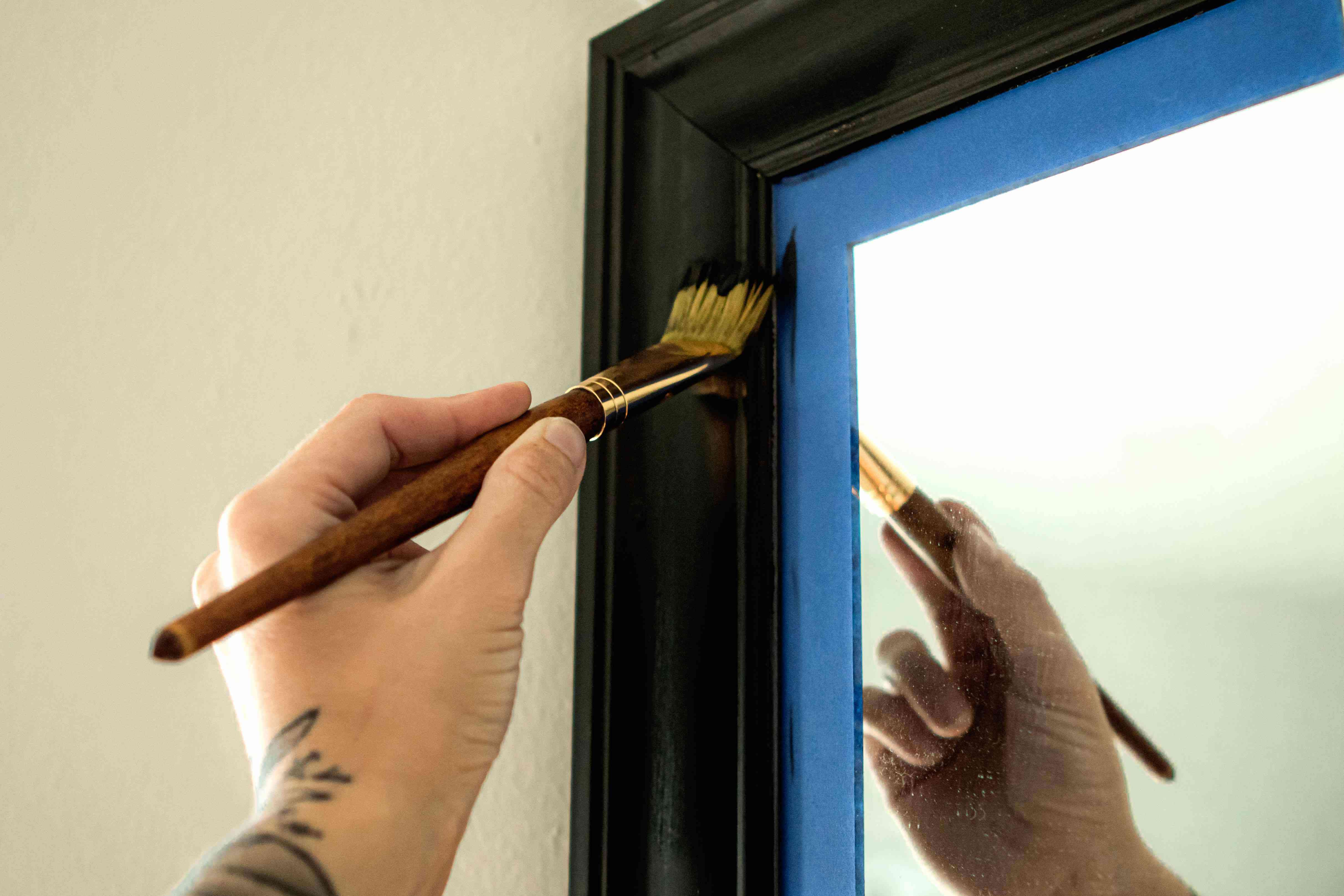 blue painter's tape is attached to mirror while person paints frame black with paintbrush