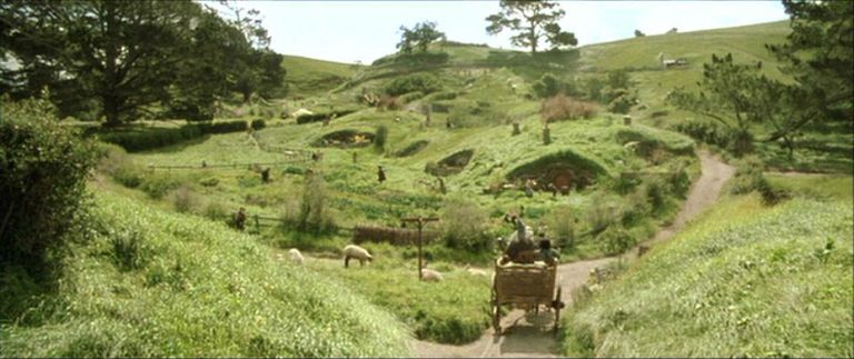 """Landscape of """"The Shire"""" from """"Lord of the Rings"""" with carriage on the road among hills and homes"""