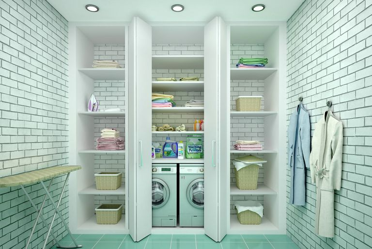White tiled laundry room with open cupboards showing washer, dryer, and laundry on shelves