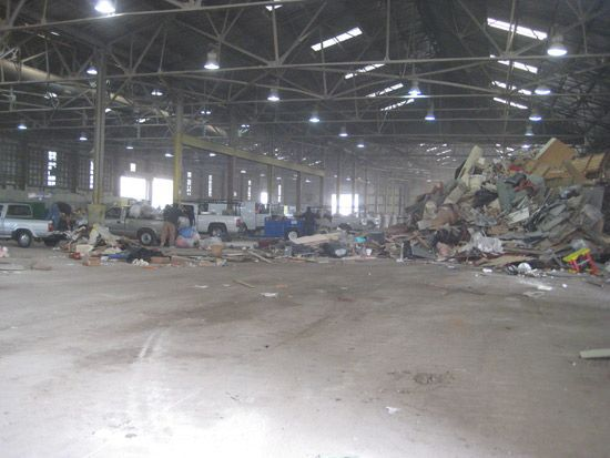 Trucks and waste inside a large warehouse facility.