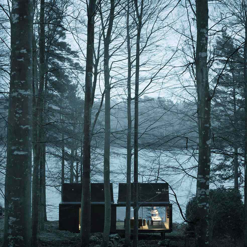Faraway view of a VIPP shelter in the forest on a lake at night