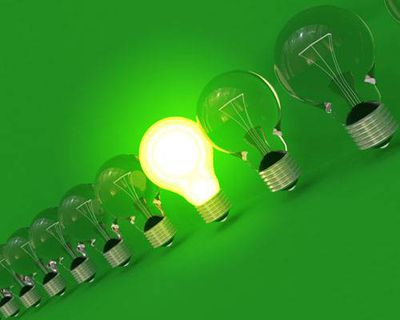 A group of lightbulbs with one illuminated
