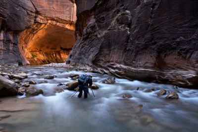A hiker walks through knee-deep water in a sandstone canyon