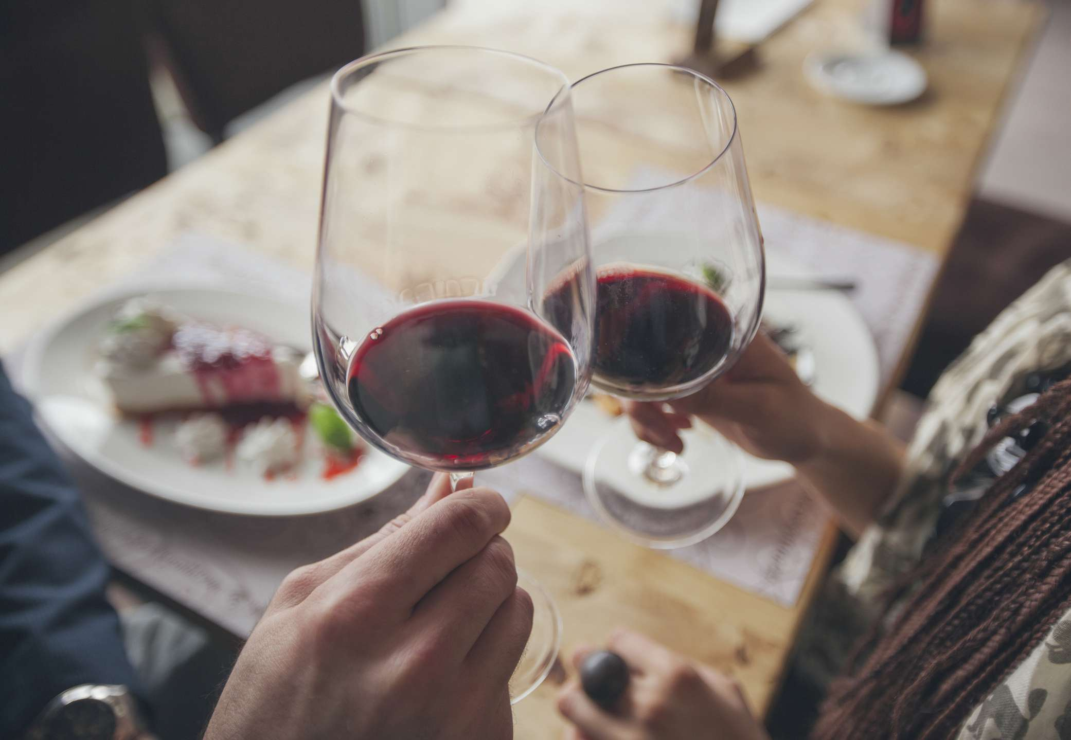 Red wine held by two people in glasses.