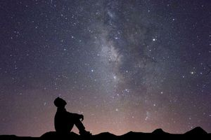 Silhouette of a person sitting on the ground looking up at star filled sky