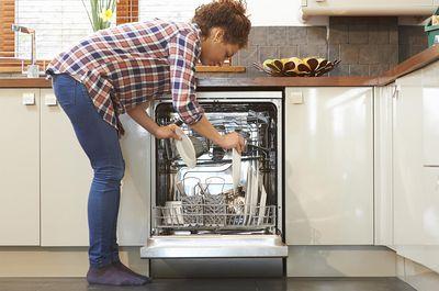 Woman unloading dish washer