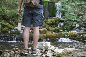 guy with water bottle and backpack goes hiking outside in rocky creek near waterfall
