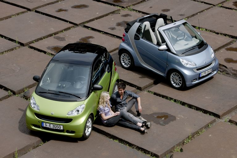Two people sitting outside of two Smart cars.
