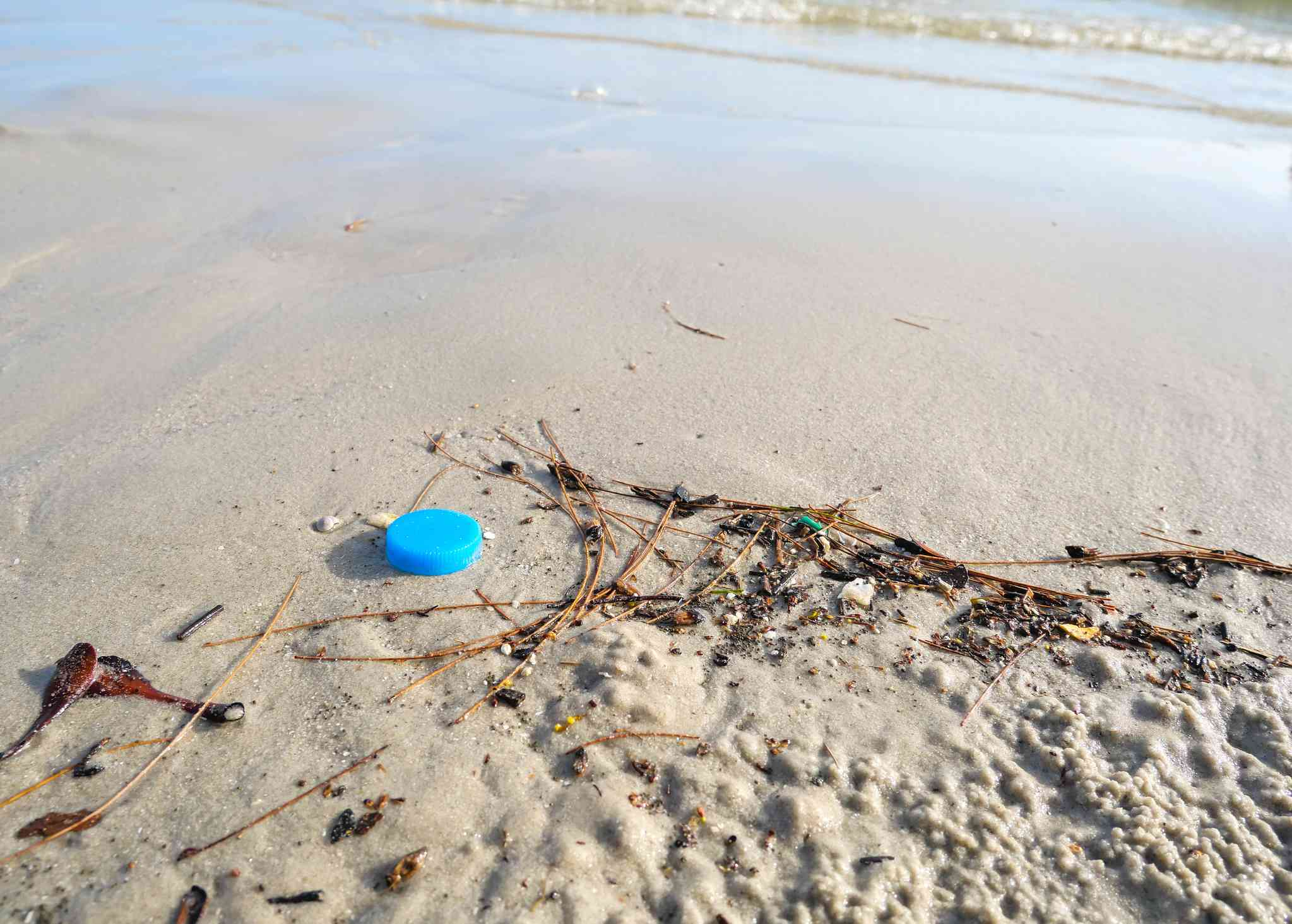 Plastic bottle cap debris on the beach