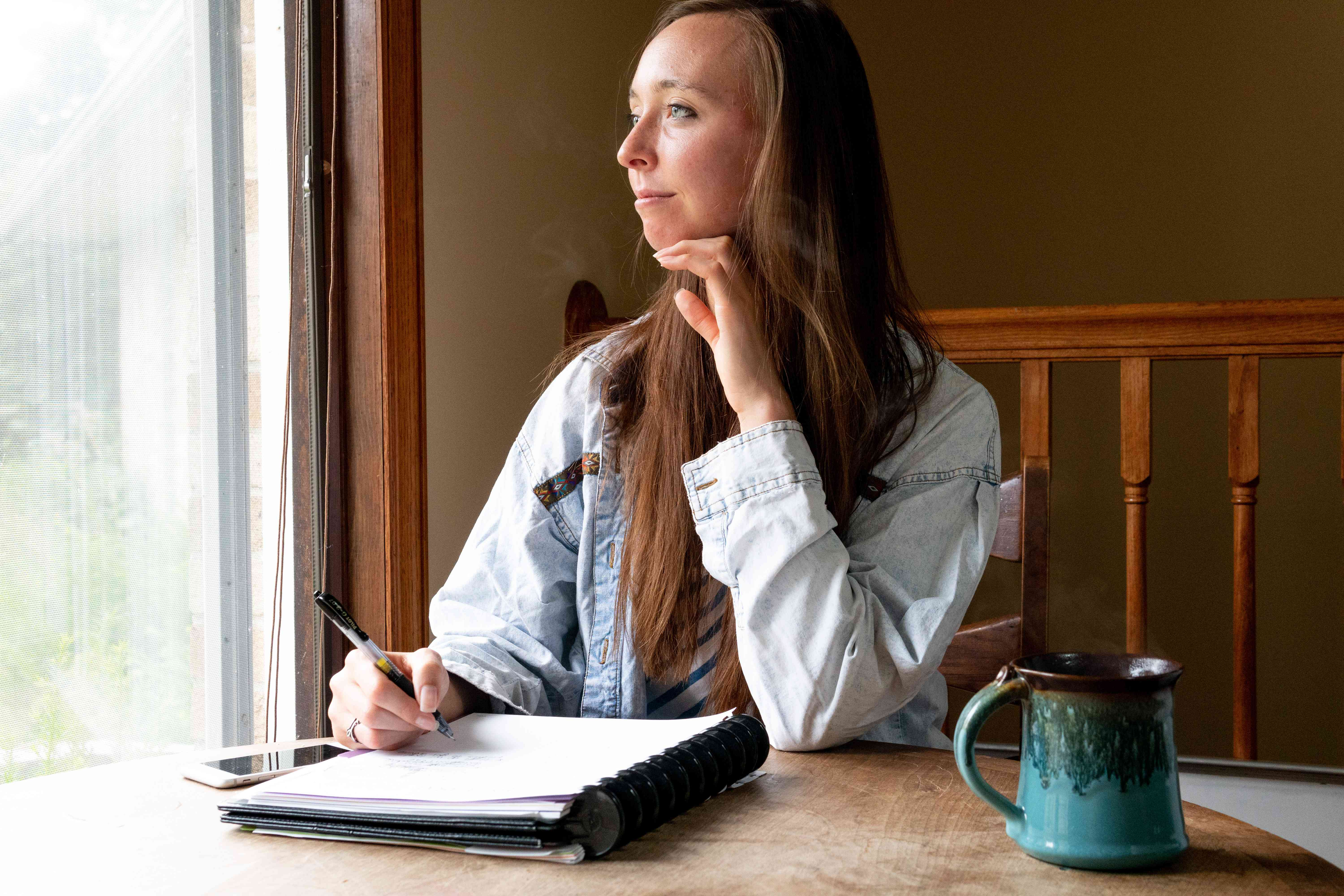 a young woman with notebook and pen stares out window contemplating