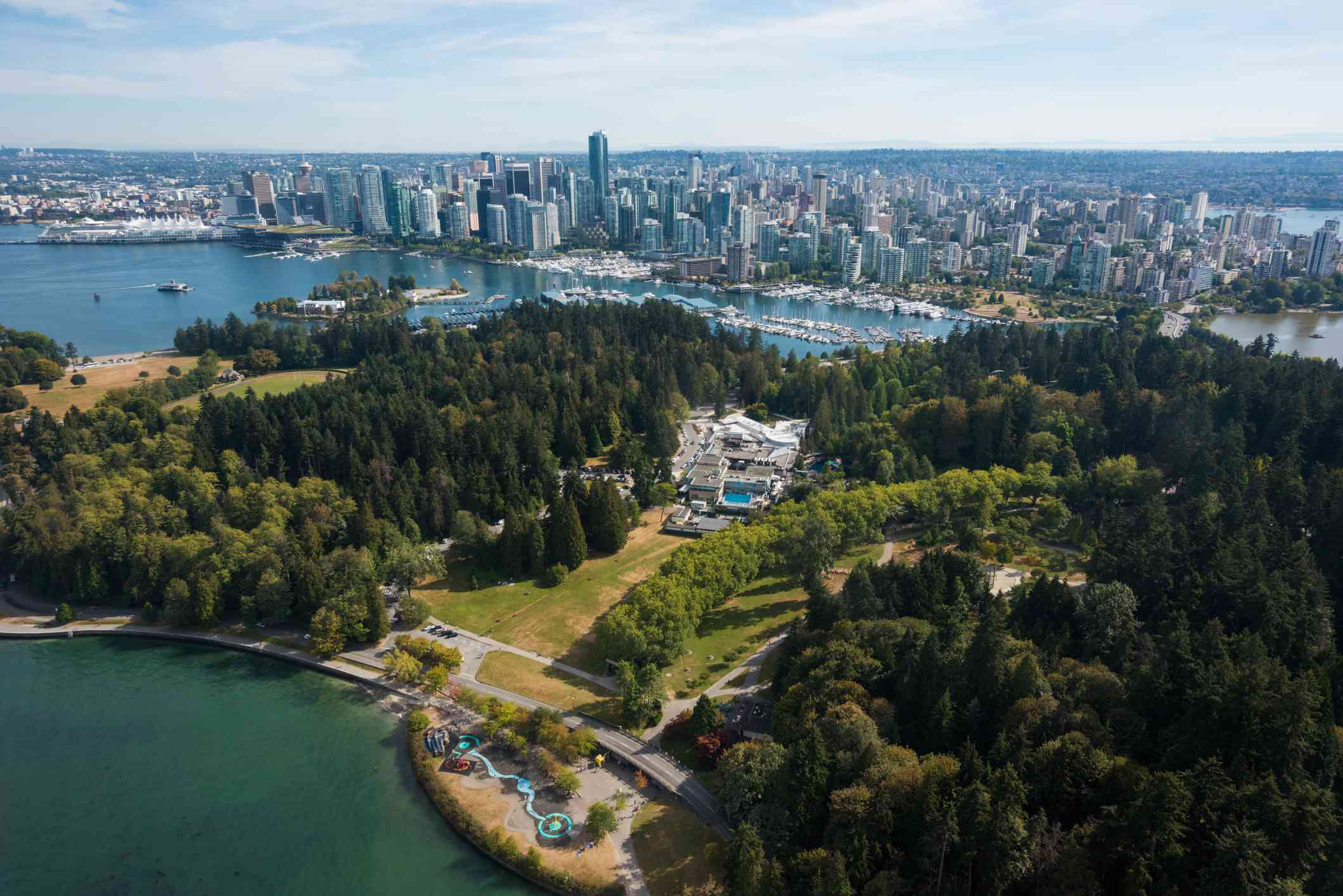 Aerial view of Stanley Park covered with lush green trees and surrounded by water with downtown Vancouver in the background
