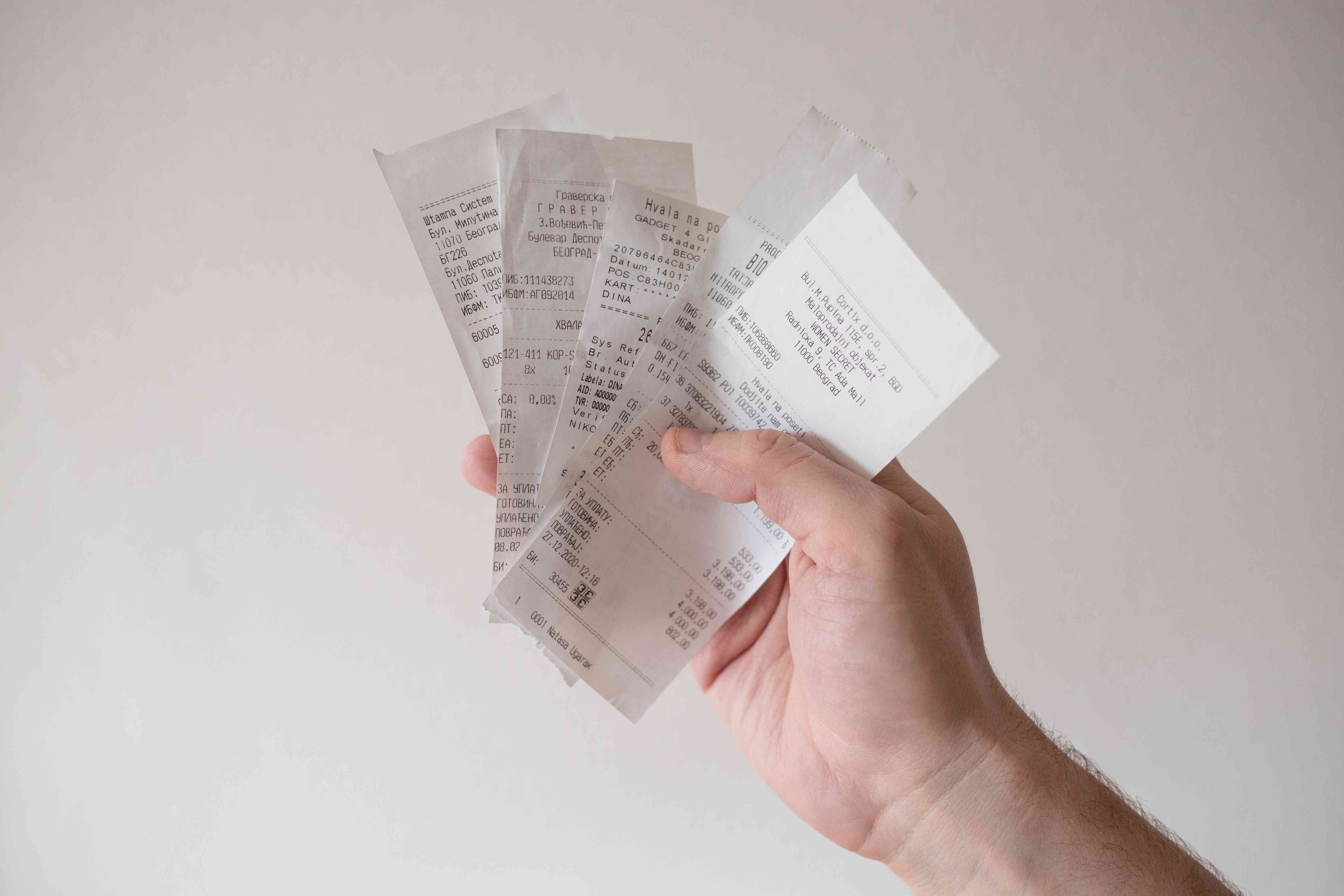 hand holds multiple receipts against blank white wall
