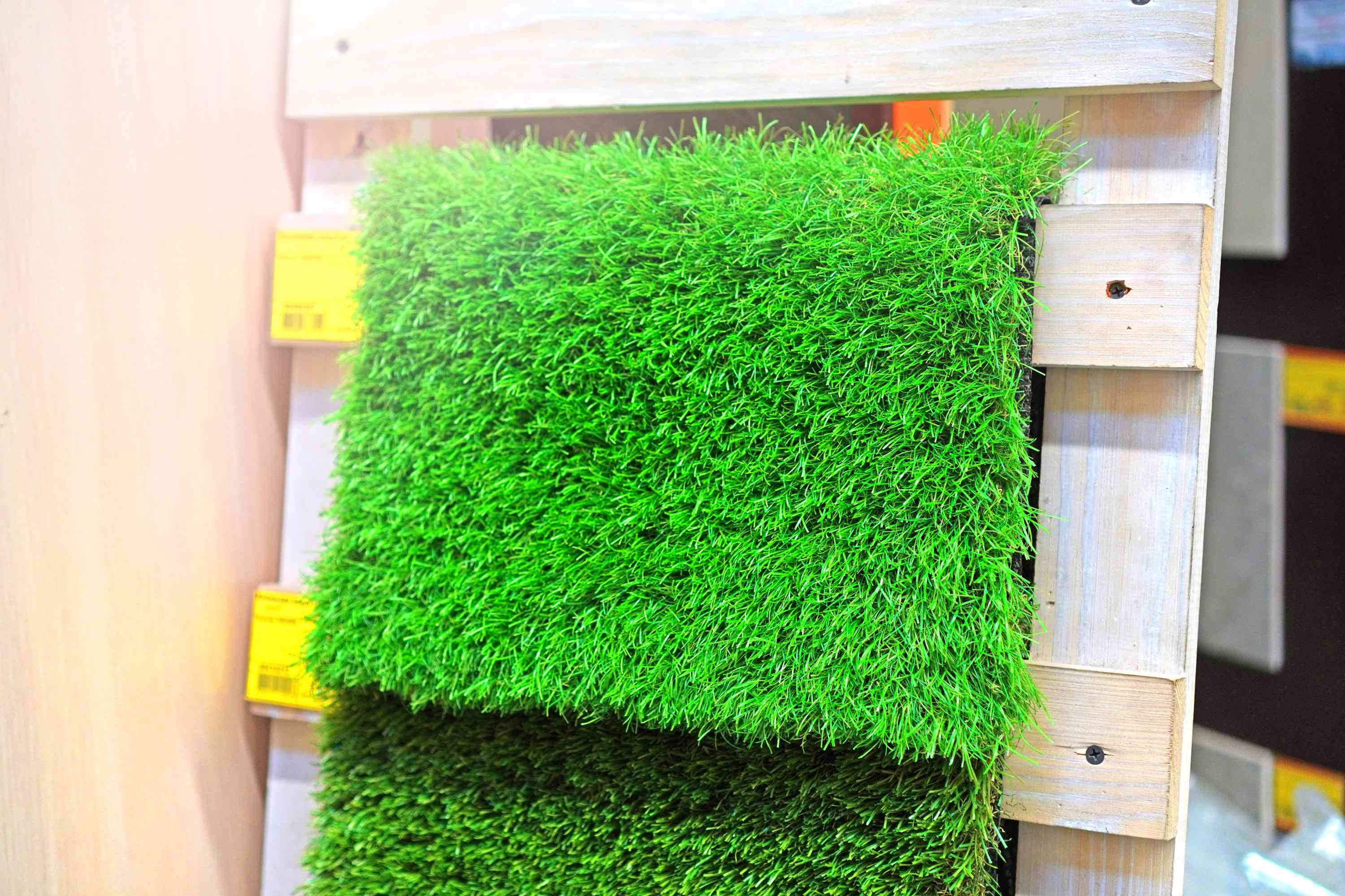 Artificial grass sample hanging on a wood display.