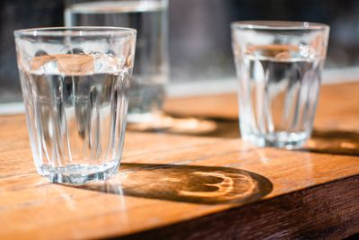 Three glasses of water on a wooden tabletop