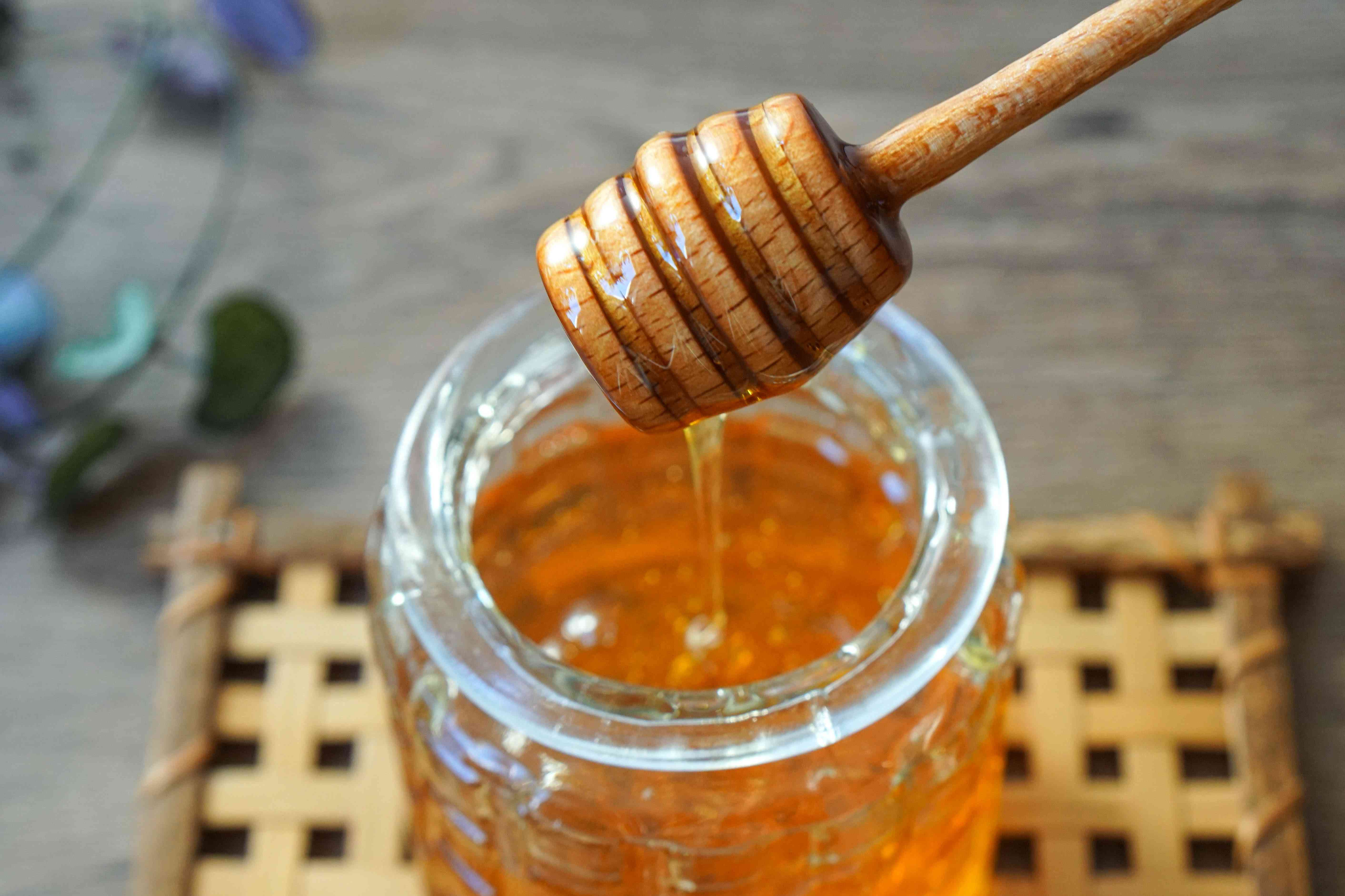 wooden honey dipper is pulled out of glass container dripping with honey