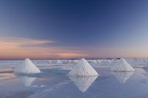 Triangular salt piles on Uyuni salt flat, reflecting the sunrise