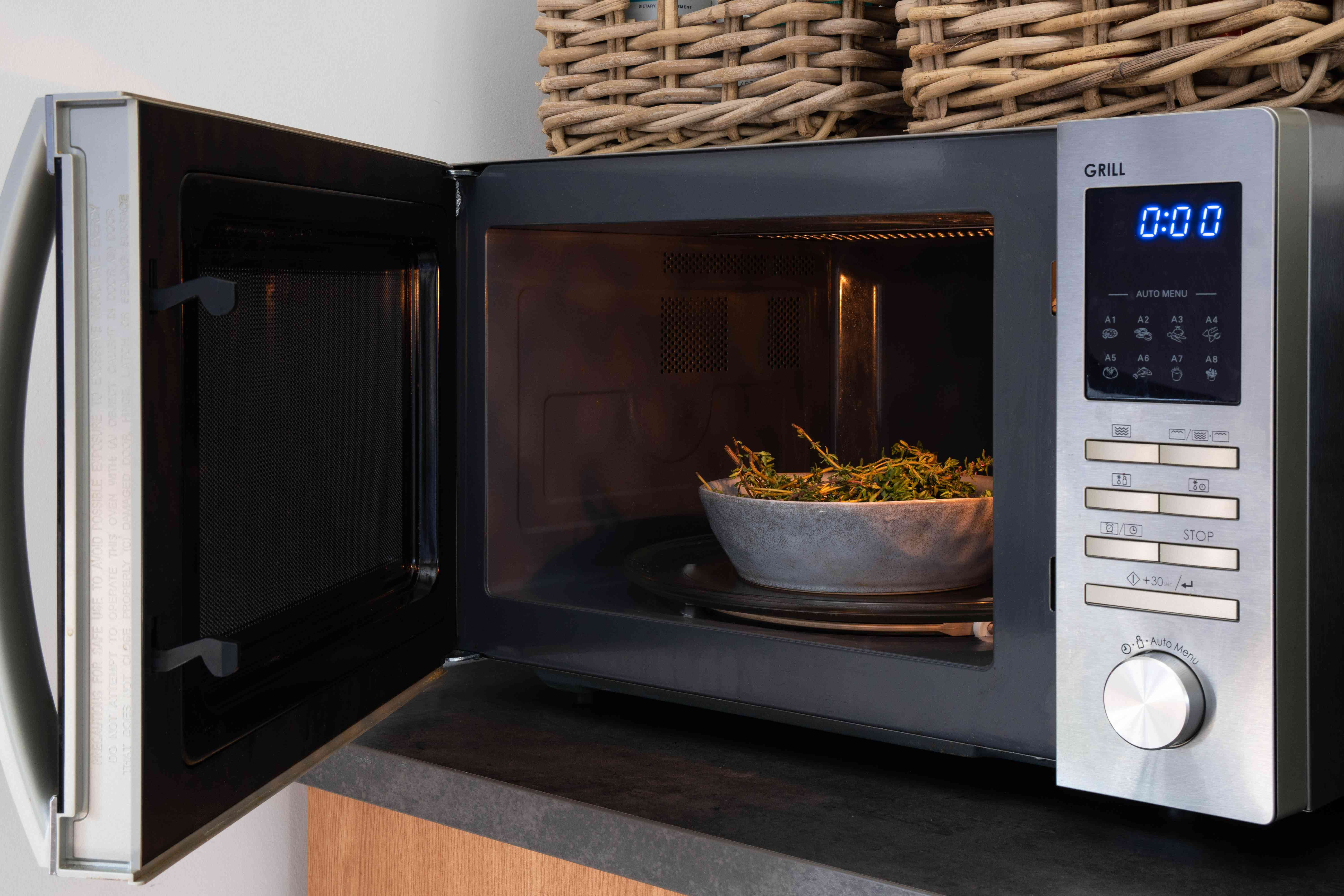 herbs being dried in a microwave with the door ajar