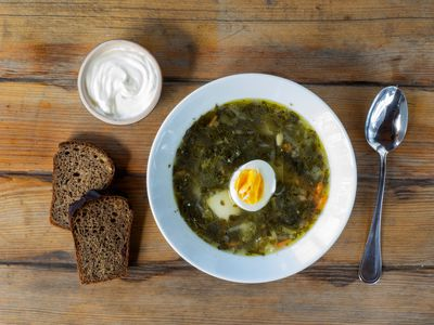 Sorrel Soup With Boiled Egg And Stinging Nettles On Table