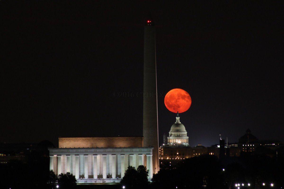 a full, orange moon appears over DC horizon