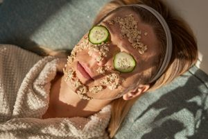 blonde woman relaxes with cucumber eye masks and diy oatmeal scrub on face