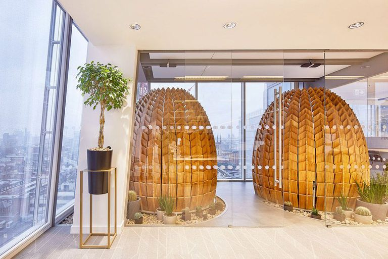 Two wooden pods in a glass-walled room
