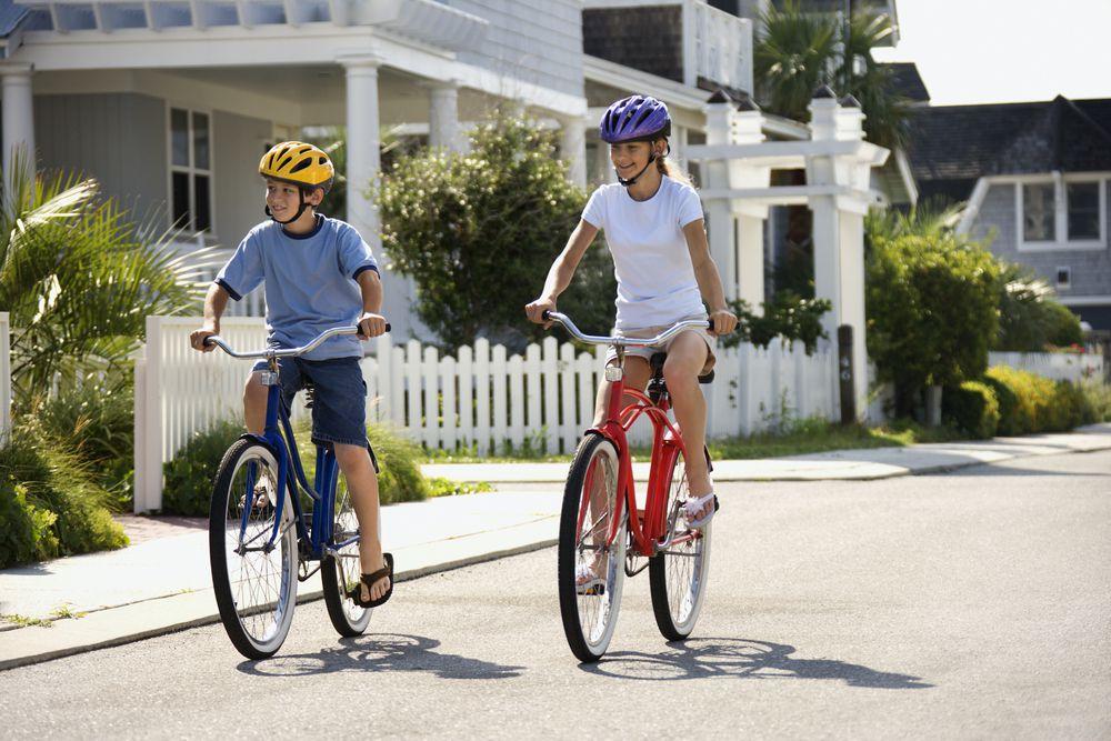 two kids riding bikes in a neighborhood