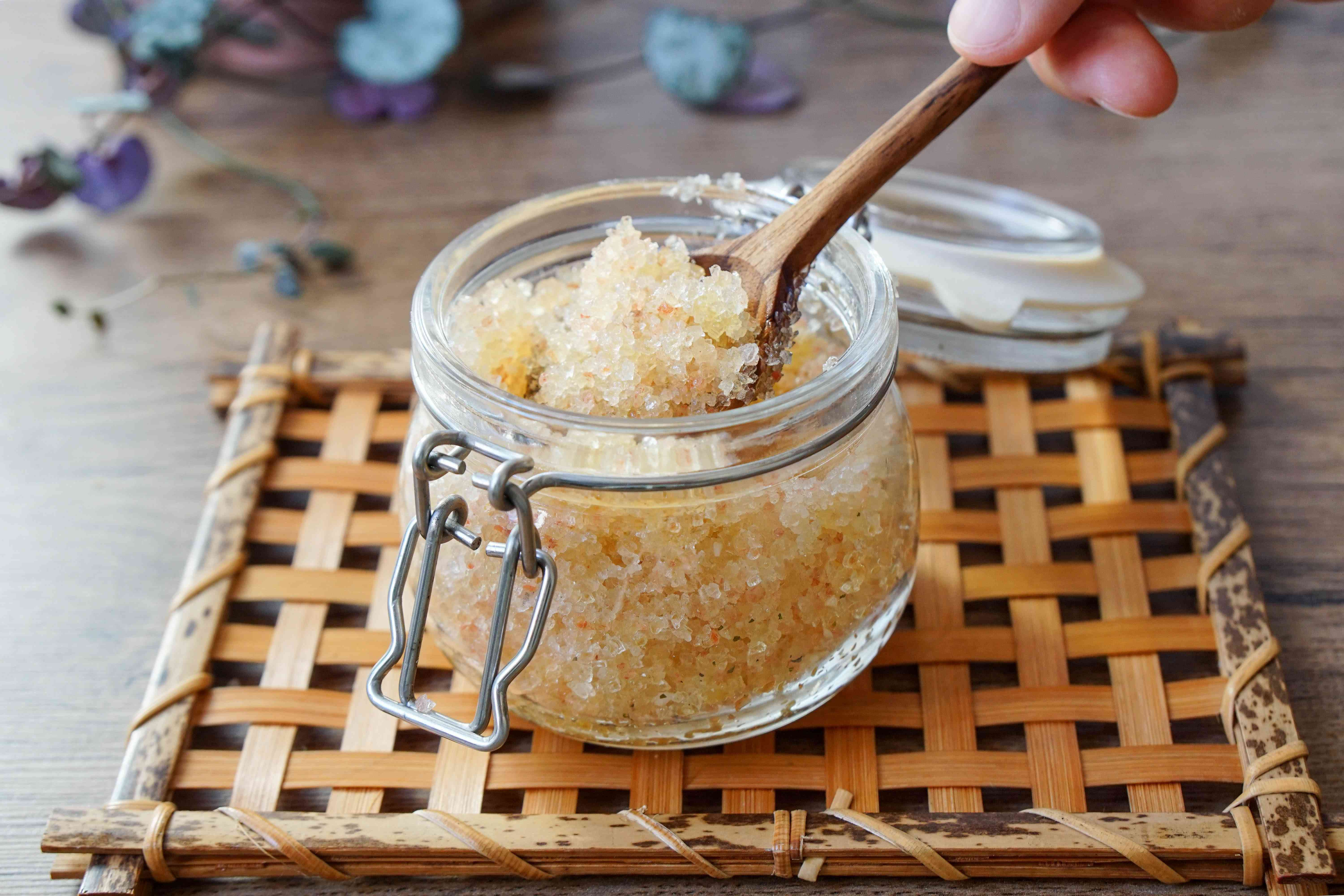 salt scrub mixture is spooned into glass container with spring-loaded lid