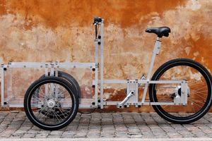 Cargo bike parked against an orange wall