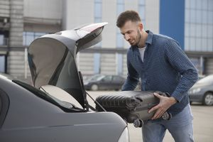 Young man putting a suitcase in a car trunk