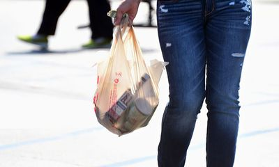A woman in Monterey Park, California, carries her groceries in a plastic bag
