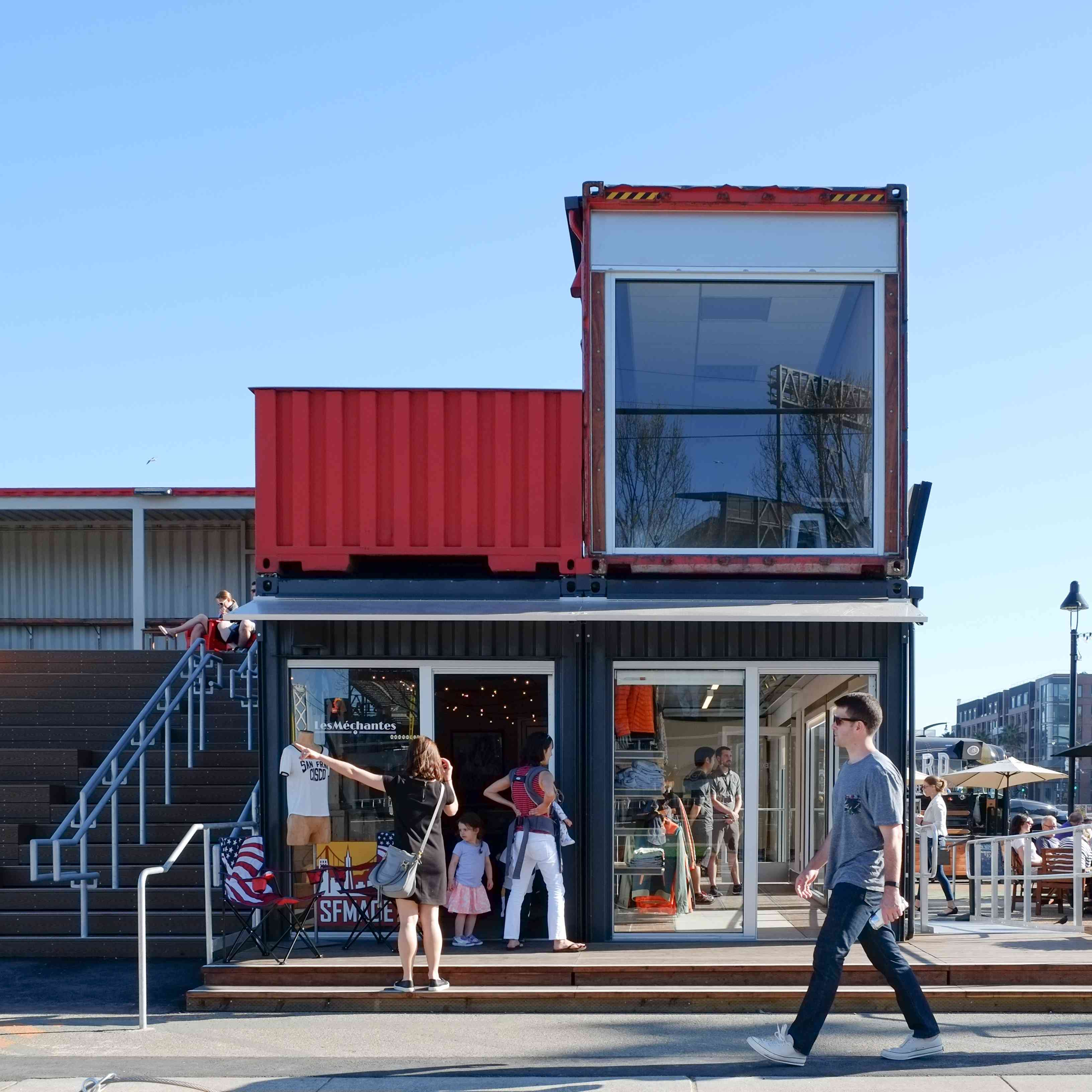 Street view of shipping containers stacked atop a storefront
