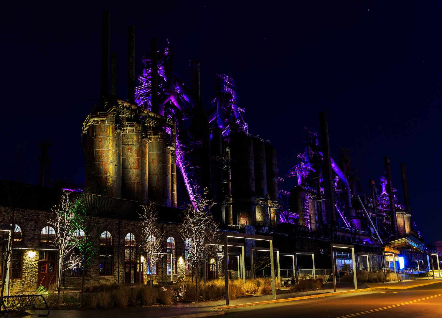The renovated SteelStacks entrance at night with the furnaces lit up in purple