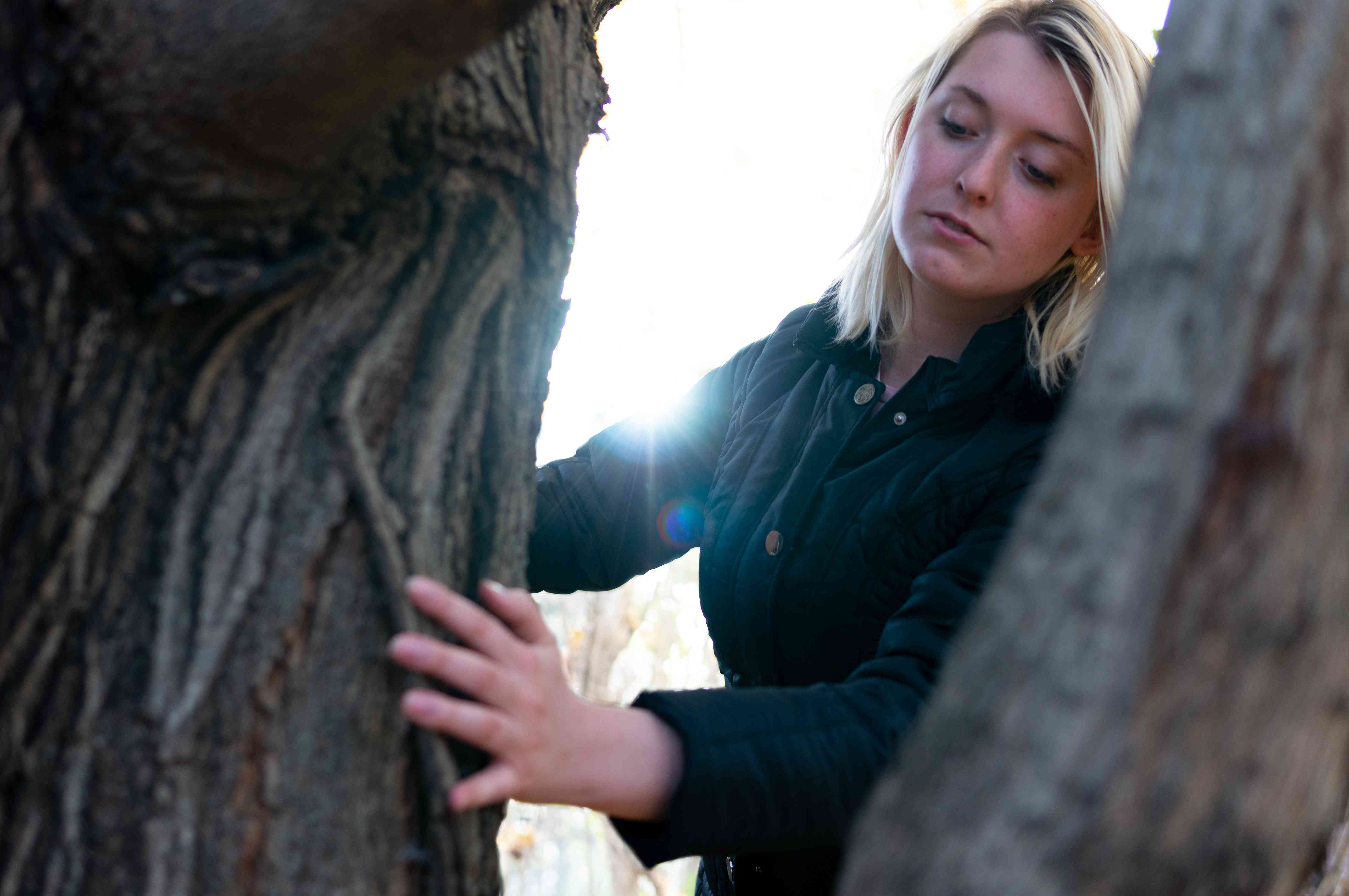 woman investigates trees outside for maple