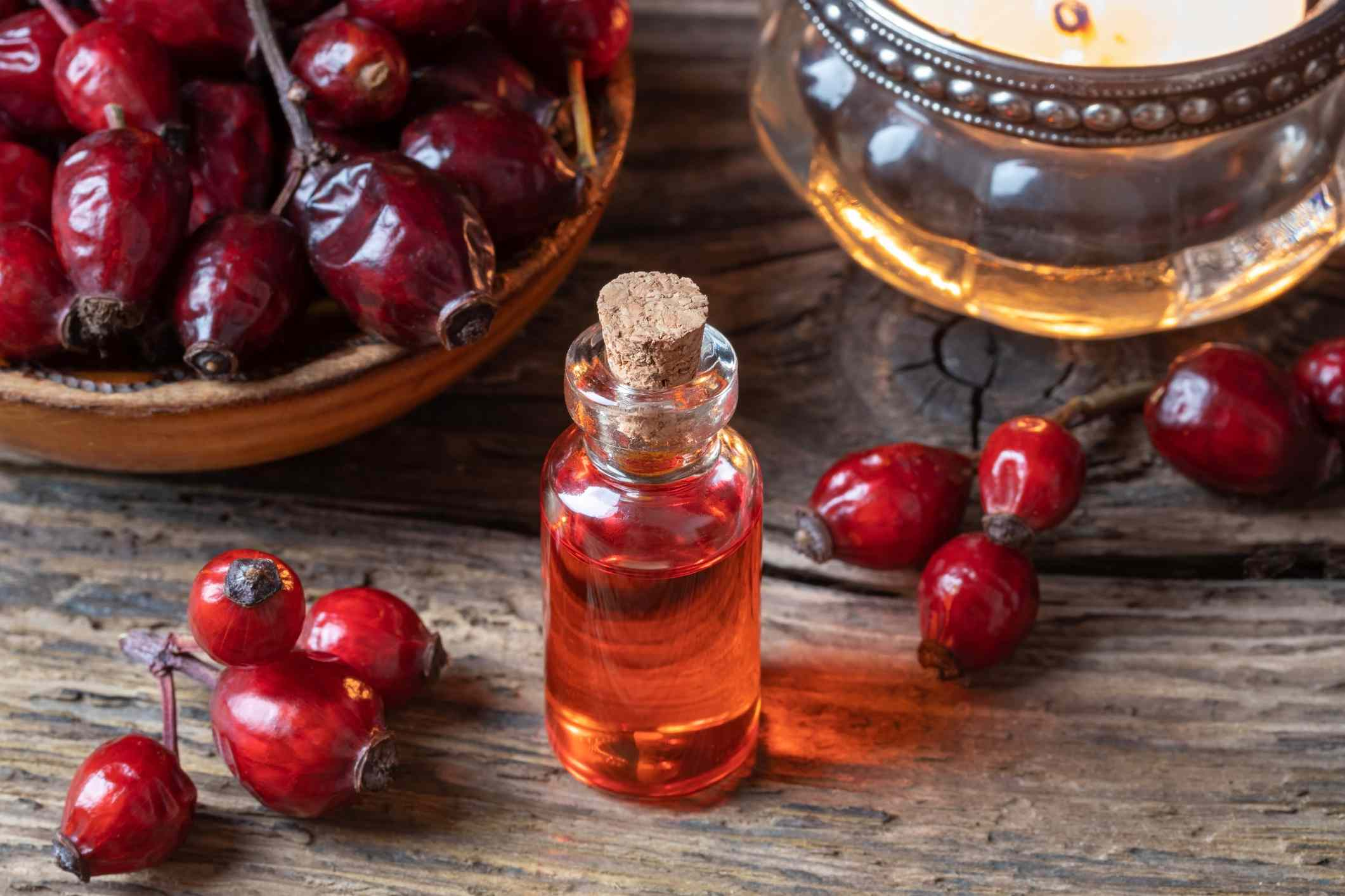A bottle of rose hip seed oil with dried rose hips on a table