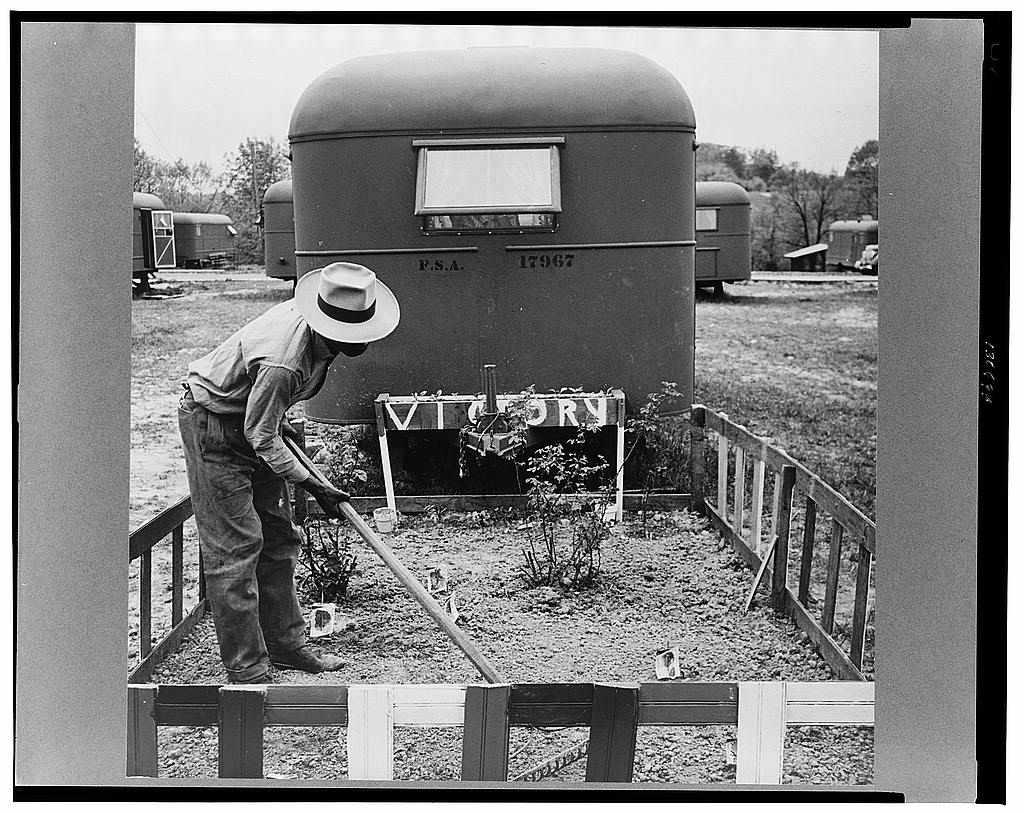Man working a small fenced garden behind a trailer