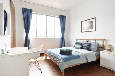 Clean guest room with folded towels at the end of the bed