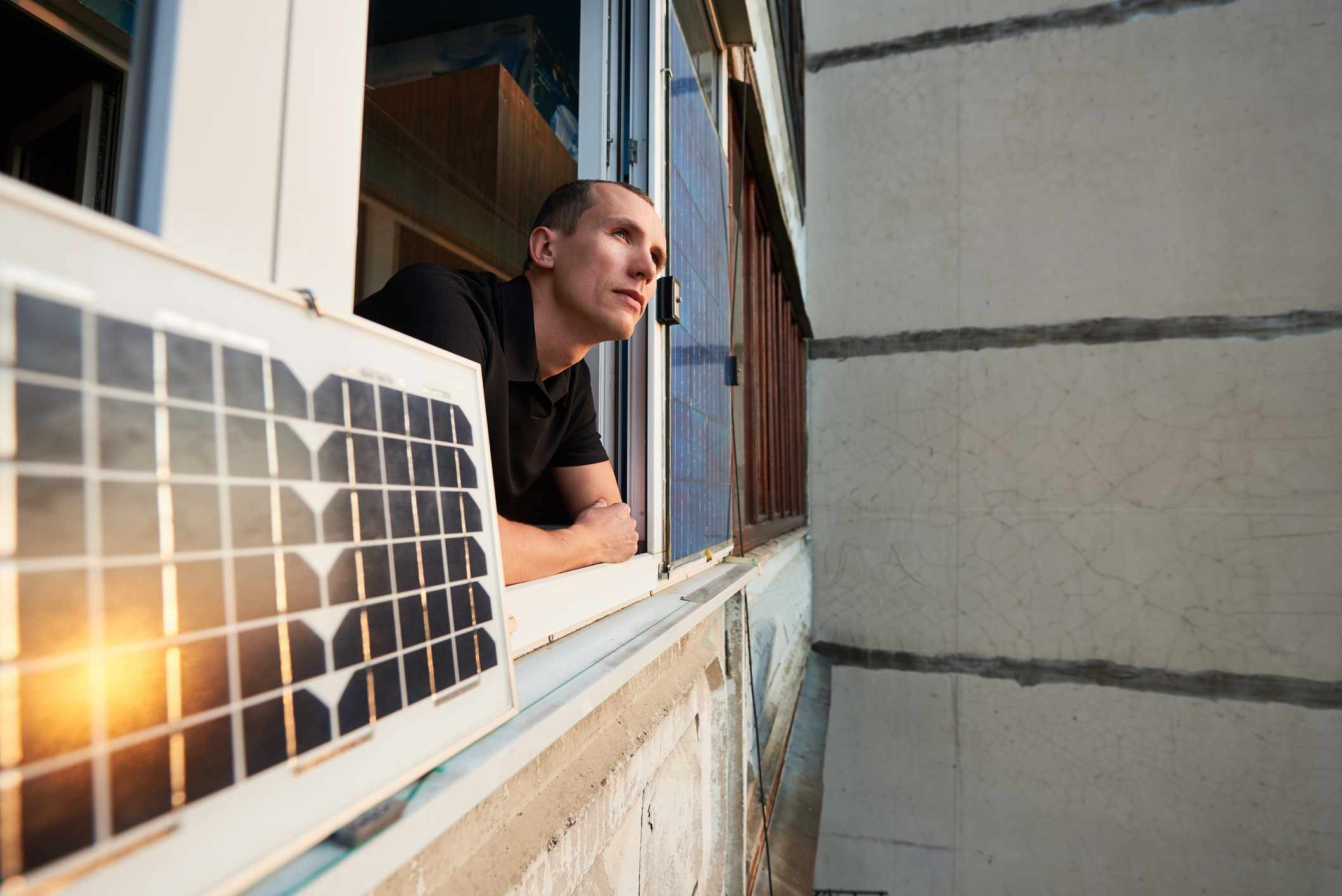 A man leans out an apartment window next to a portable solar panel attached to the window ledge; the sun's reflection is visible in the panel..