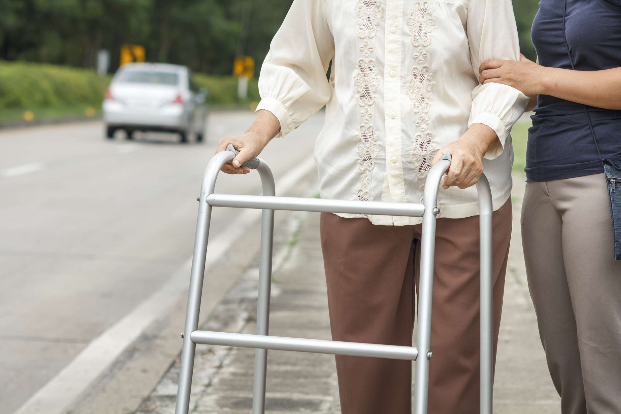 An elderly woman using a walker and assistant crossing a road with a car.