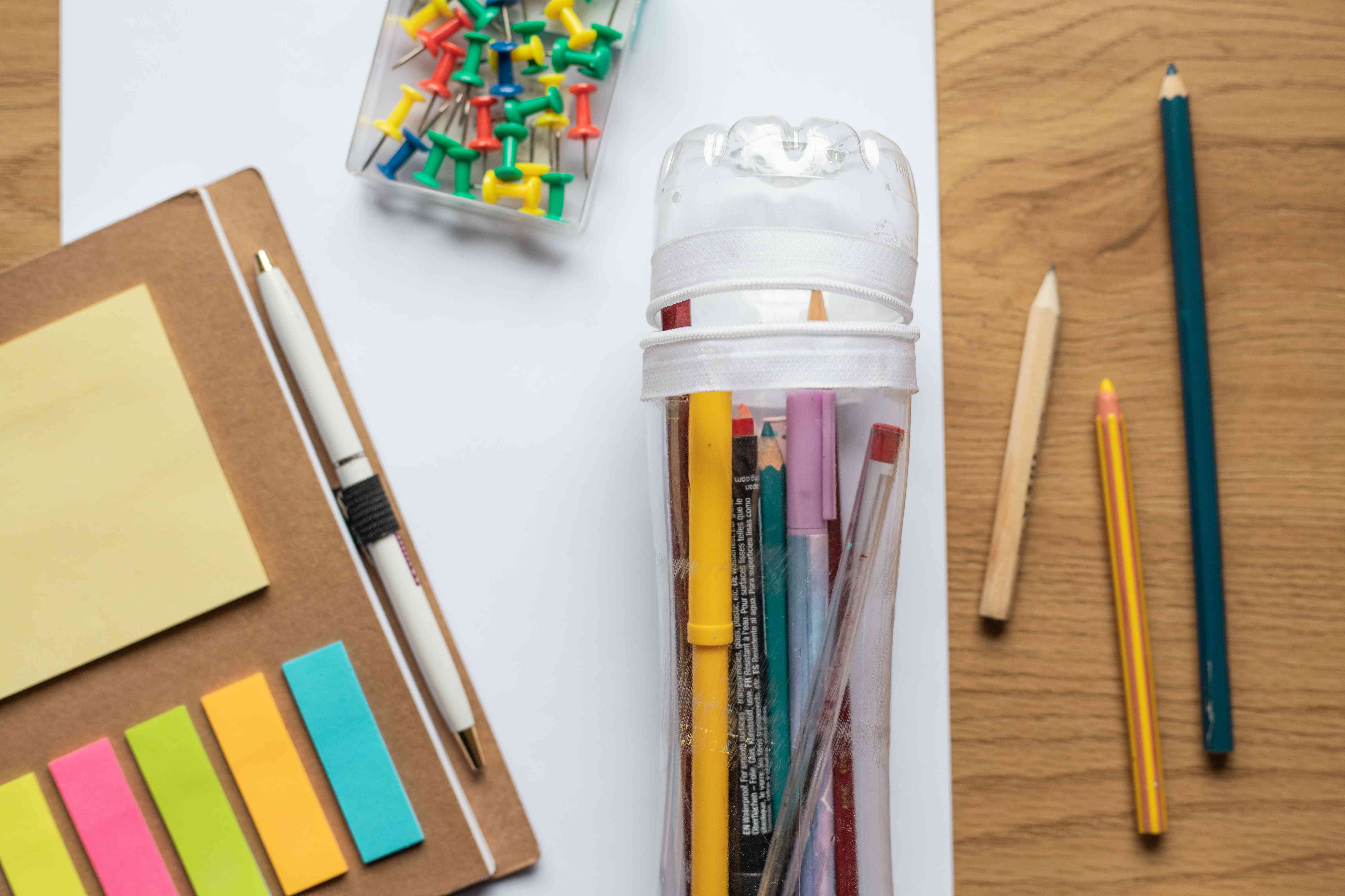upcycled water bottle turned into pencil storage with glued on zipper