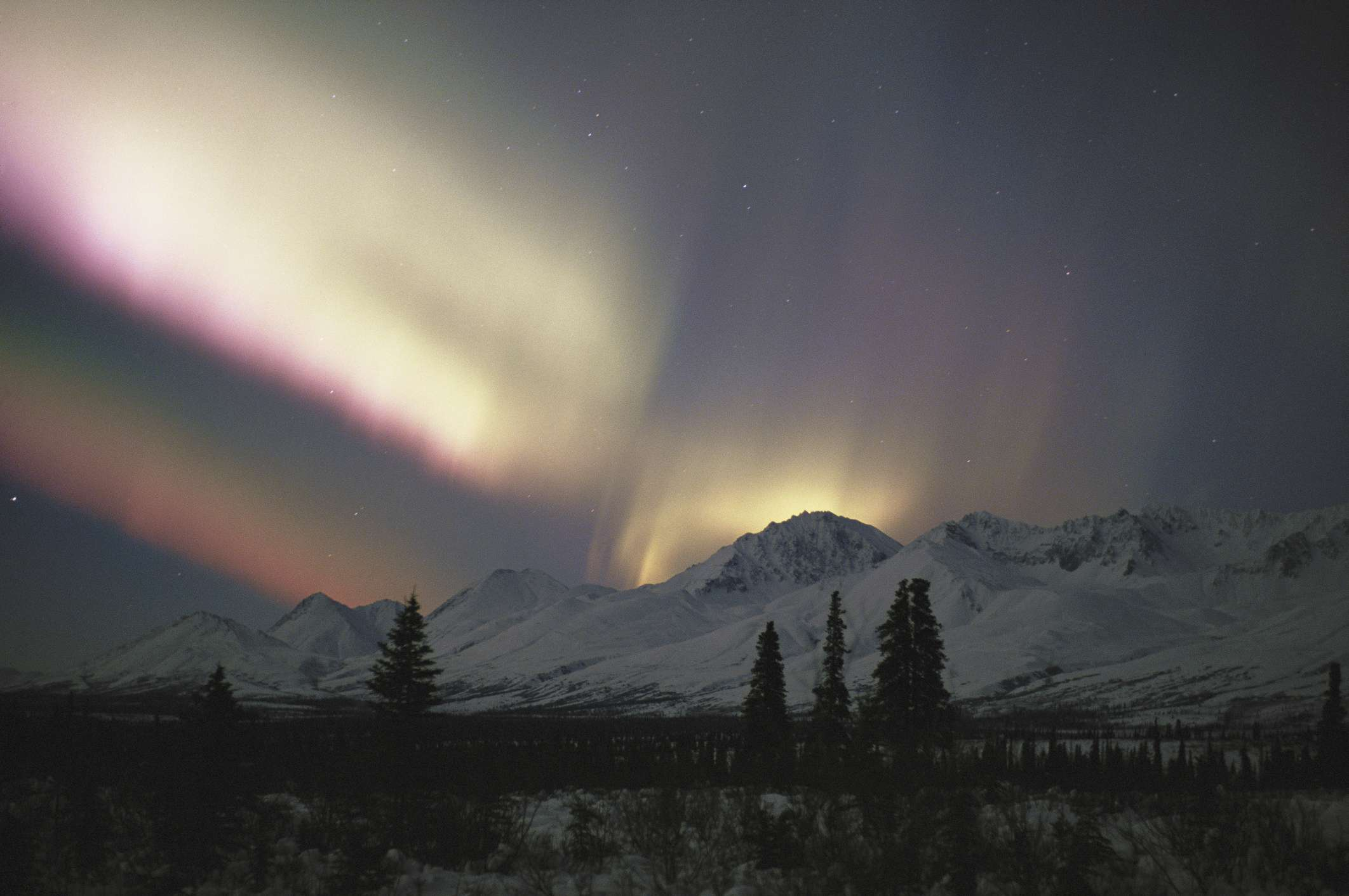 White and pink northern lights over snowy mountains