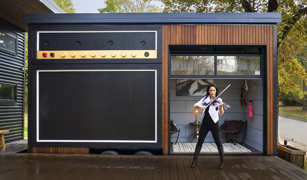 Woman playing violin on deck in front of the mobile part of the tiny house